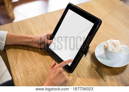 Close-up of woman using digital tablet with blank screen in cafe