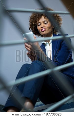 Businesswoman using mobile phone while sitting on steps at conference centre