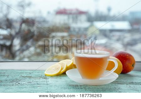 Glass cup of hot tasty tea with sliced lemon on wooden windowsill