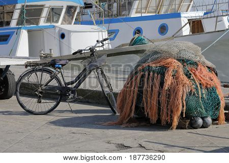 Fishing nets on the harbor to dry near the fisherman's bicycle