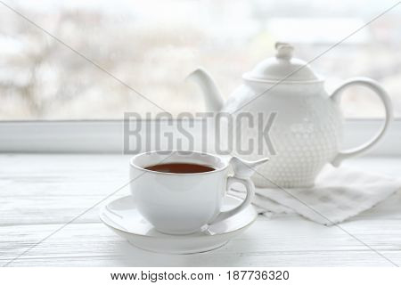 Cup of hot drink with teapot on wooden windowsill