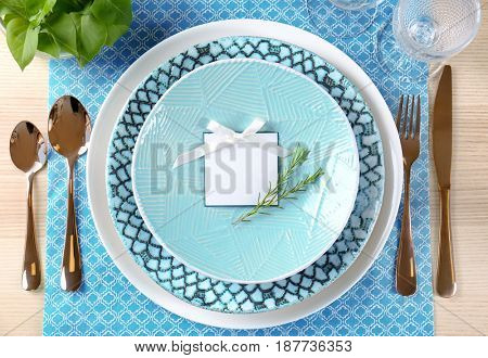Beautiful table setting, blank card and floral decor on blue napkin