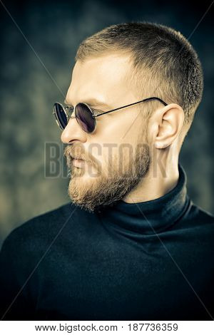 Handsome bearded man wearing round sunglasses. Male fashion.