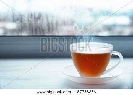 Glass cup of hot tasty drink on wooden windowsill