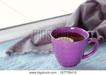 Ceramic cup of hot tasty tea with lemon and plaid on wooden windowsill