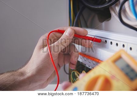 Young electrician measuring voltage in distribution board