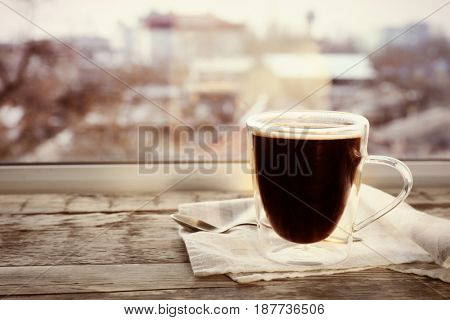 Glass cup of delicious hot coffee on wooden window sill