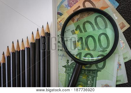 Pencils arranged as rise up graph and magnifying glass on pile of Euro banknotes as financial concept.
