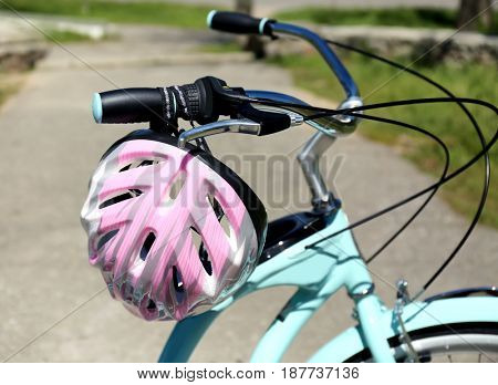 Bicycle handlebar with helmet and pavement on background