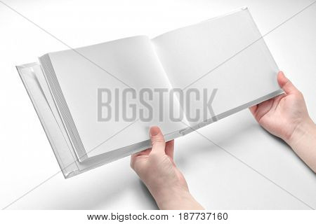 Female hands holding book with blank pages on white background