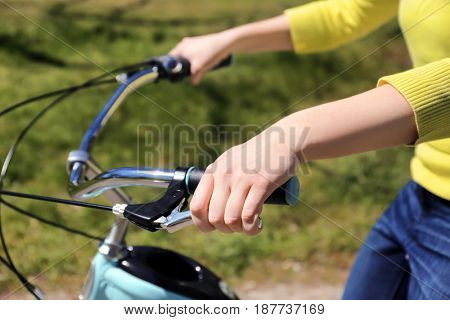 Young woman pressing bicycle brake lever on blurred background
