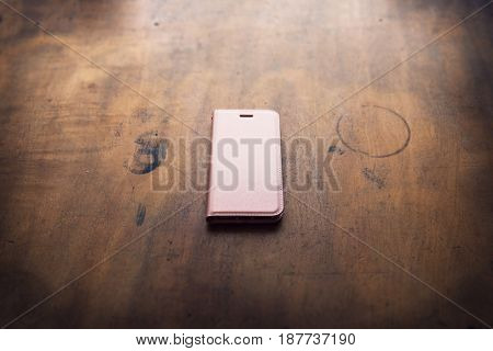 Smart phone in a pink wallet type or flip open type case, on a grungy wooden desk. Shallow depth of field.