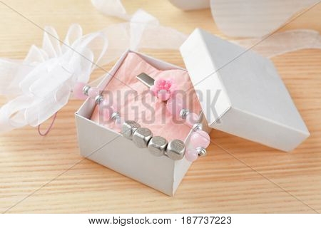 Cute pacifier clip with place for baby name in gift box on table