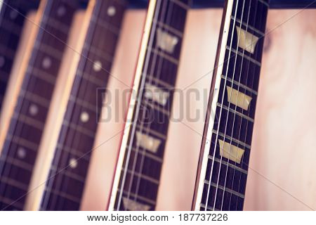 Electric guitars necks on a guitar rack in a studio Extremely shallow depth of field.
