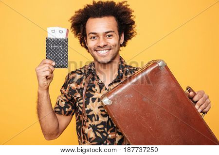 Image of young happy african man standing isolated over yellow background. Looking at camera holding passport and suitcase.