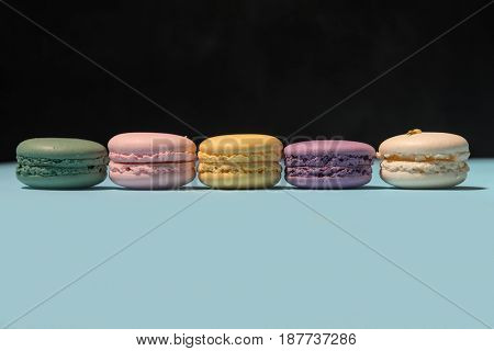 Image of five sweet colorful macaroons on blue table over black background.