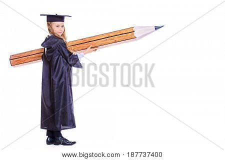 Educational concept. Happy schoolgirl in academic hat and a gown posing with a huge pencil. Isolated over white. Full length portrait.
