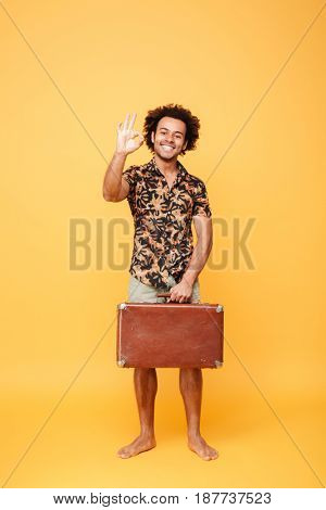 Full length portrait of a cheerful young afro american man holding suitcase and showing ok gesture isolated over yellow background