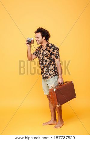 Side view full length portrait of a happy young african tourist man in summer clothes taking a picture with a retro camera isolated over yellow background