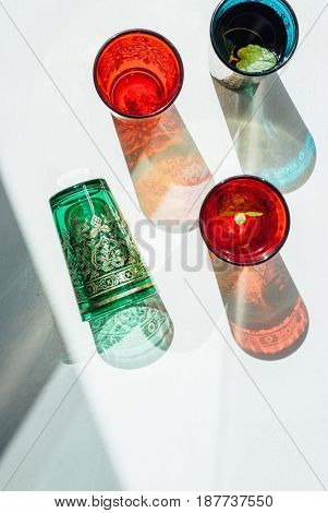 Moroccan ming tea in colorful glasses. Abstract shadow and light play using colorful traditional moroccan tea glasses.