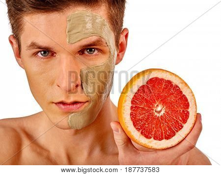 Facial mask from fresh fruits and clay for man concept. Face with treatment mud applied. Male holding grapefruit half for skin care procedure in salon. Use of fresh fruits promotes skin rejuvenation.