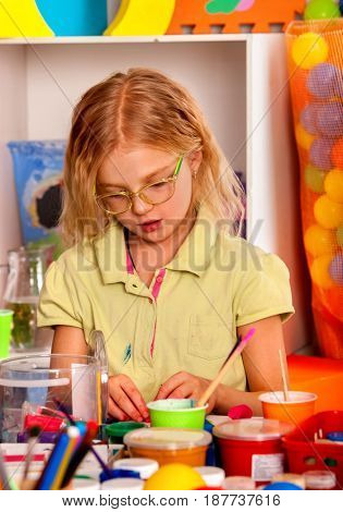 Small student girl painting in art school class. Child drawing by paints on table. Portrait of kids in kindergarten. Craft drawing education develops creative abilities of children. Crafting.