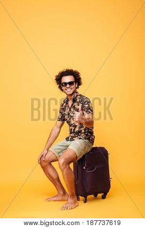 Picture of happy young handsome african man wearing sunglasses sitting on suitcase and showing thumbs up gesture isolated over yellow background. Looking at camera.