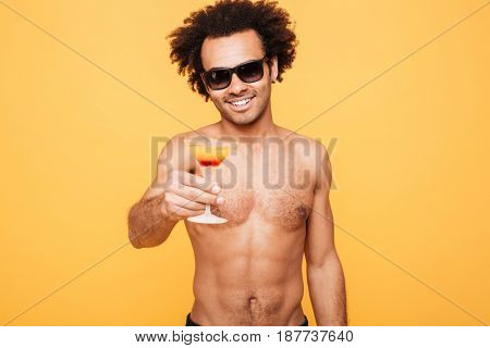 Image of young smiling african man dressed in shorts standing isolated over yellow background. Looking at camera holding cocktail.