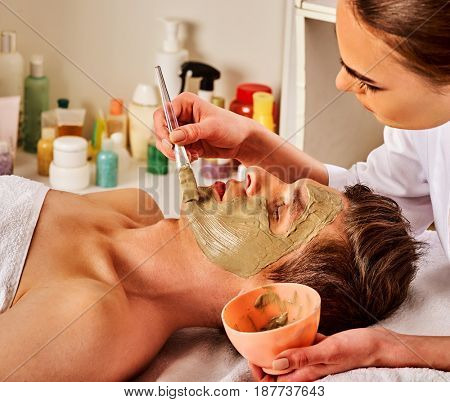 Mud facial mask of woman in spa salon. Massage with clay full face. Girl on with therapy room. Apply a mask on face with a brush. Beautician with bowl therapeutic procedure isolated background.
