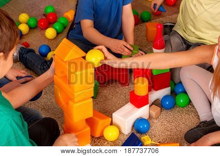 Children playing in kids cubes indoor. Lesson in primary school. Body part of girl and boy together play. Kindergarten kids sit on soft carpeton floor .