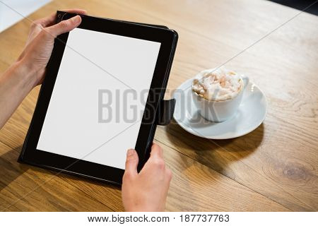 Cropped image of woman using digital tablet with blank screen in cafe