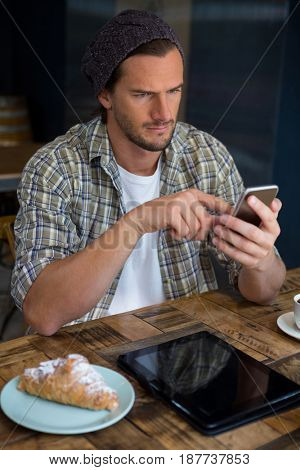 Handsome young man using mobile phone at table in coffee shop