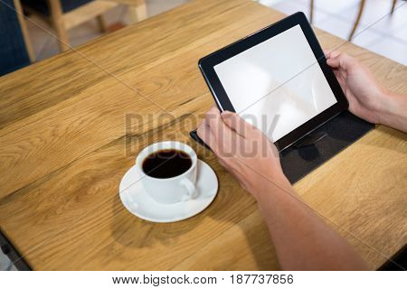 Cropped image of man using digital tablet with blank screen in cafe
