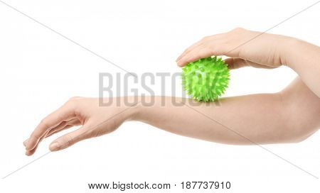 Hands of woman doing exercises with rubber ball on white background