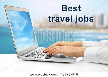 Concept of tourism and work. Woman working with laptop and text BEST TRAVEL JOBS on blurred background