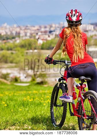 Escape urban . Bicycle girl has rest from city bustle. Woman wearing sport helmet returns home after long hike in urbanization . Respect for environment. Factory pipes in background. Back view.
