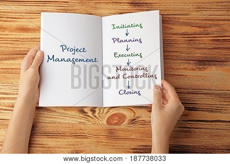 Business concept. Woman reading book about PROJECT MANAGEMENT at wooden table