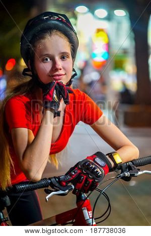 Bikes bicyclist girl wearing bicycle helmet. Outdoor portrait of happy teenager returns from nightclub .Lights and neon sign of night city street in background.