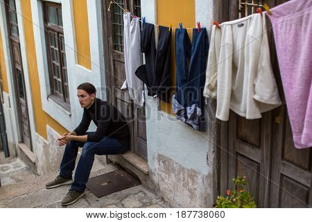 Young fashionable guy on the streets of a European town, sitting on the porch of the house.