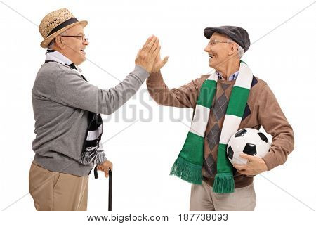 Two elderly soccer fans high-fiving each other isolated on white background