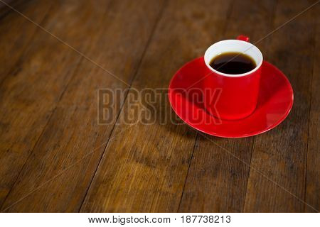 Close-up of red cup and saucer on table in coffee shop