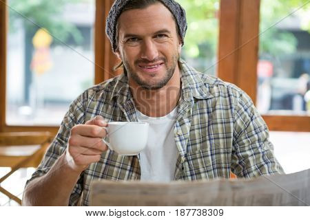 Portrait of smiling young man holding coffee cup in cafe