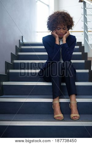 Worried businesswoman sitting on steps at conference centre