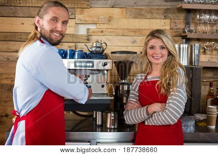 Portrait of male and female baristas standing by coffee machine at cafeteria