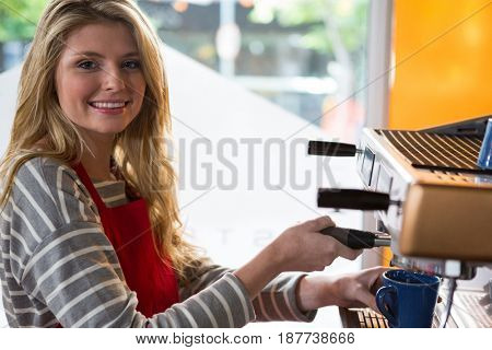 Portrait of smiling female barista preparing coffee with machine in cafeteria