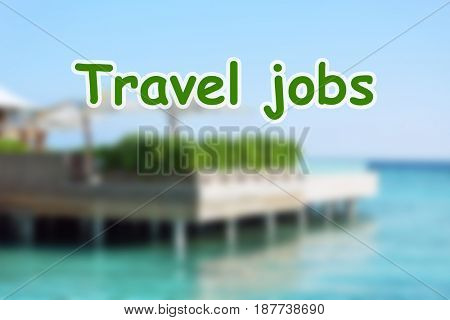 Concept of tourism and work. Text TRAVEL JOBS and blurred resort on background