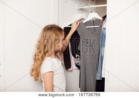 Child chooses clothes from the closet. Happy girl
