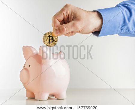 man put bitcoin coin in classic pink piggybank