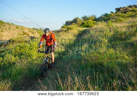 Cyclist in Red Jacket Riding the Mountain Bike on the Beautiful Spring Trail. Travel and Adventure Sport Concept
