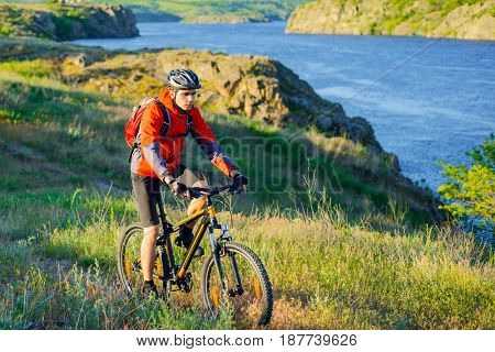 Cyclist in Red Jacket Riding the Mountain Bike on the Beautiful Spring Trail above Blue River. Travel and Adventure Sport Concept